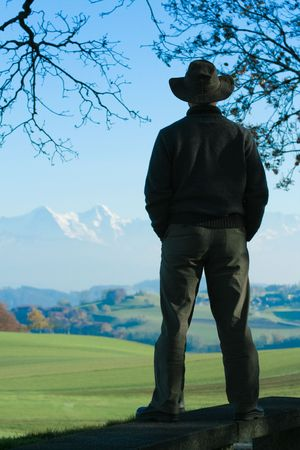 Silhouette of a man contemplating a distant chain of mountains and pastures, in Fall. Banque d'images
