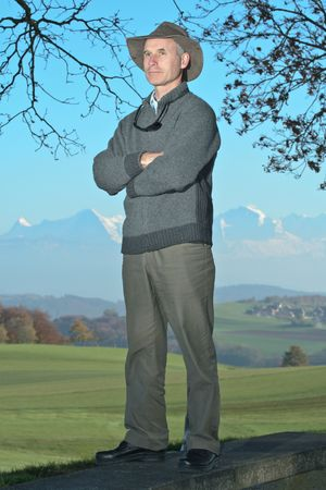 A man stands with crossed arms, against a background of farmland and a chain of mountains, in Fall.
