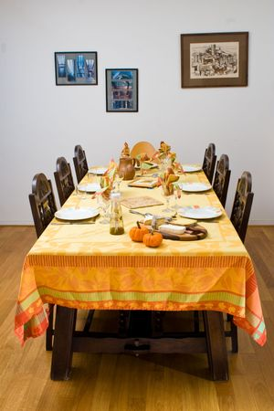 A dinner table set with festive decorations, against a wall with pictures.