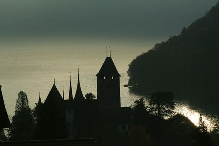 A castle tower silhouetted against a shimmering lake in the early morning Stock Photo