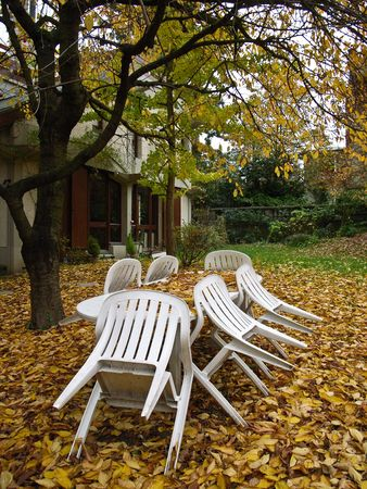 White plastic garden furniture stored for the winter, in an Autumn environment