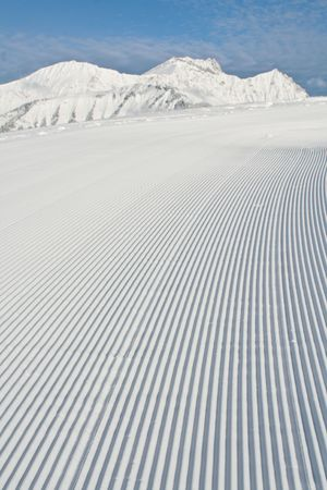 Tracks made by a snow grooming machine on a ski slope in the Alps. Stock Photo
