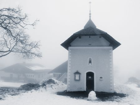 A small church surrounded by snow, with a half-melted snowman in front of the entrance.