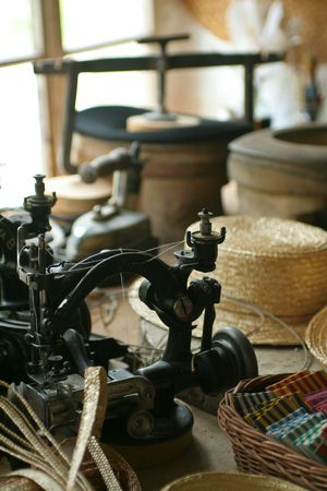 Old-fashioned hat-making shop with old-time sewing machine. Stock Photo