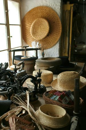 Old-fashioned hat-making shop with straw hats and an old-time sewing machine.