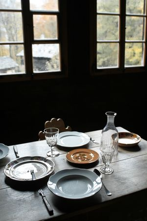 settler: Rough plank dining table set with antique cutlery, plates and glasses. Stock Photo