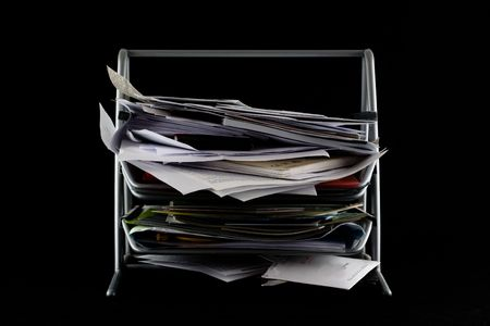 secretary tray: In-basket overflowing with papers,mail and other documents. Isolated on black background. Stock Photo