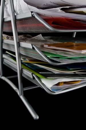 In-basket overflowing with papers,mail and other documents. Isolated on black background. Stock Photo