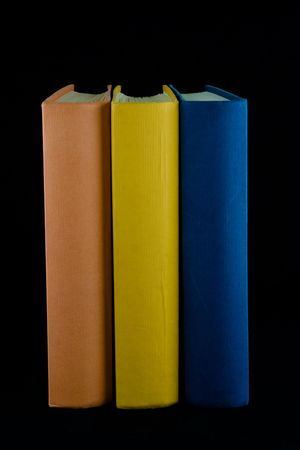 Three books,with orange, yellow and blue spines, lined up in a row. Isolated against black background. Stock Photo