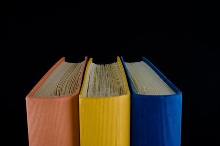 Closeup of three books,with orange, yellow and blue spines, lined up in a row. Isolated against black background.