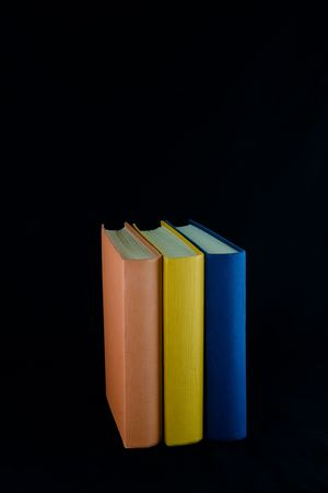 Three books,with orange, yellow and blue spines, lined up in a row. Isolated against black background. Banque d'images