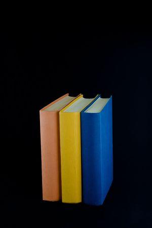 Trois livres, à l'orange, le jaune et le bleu épines, alignés en une rangée. Isolé sur le fond noir. Banque d'images - 2482914