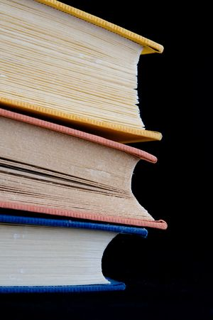 Closeup of three books,with yellow, orange, and blue covers, together in a stack. Isolated against black background.