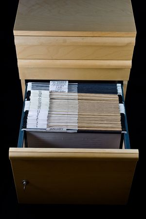 Wooden rolling file cabine t with a drawer opened, showing 43 hanging folders.