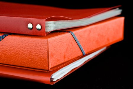 A stack of red file folders, on a black background