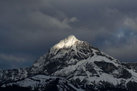 A sunbeam illuminates the peak of a tall mountain in the alps, as a darkness approaches