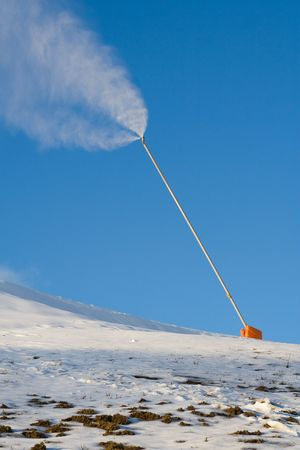 A snow canon produces snow on a partly bare ski slope, with patches of dirt visible in the foreground.