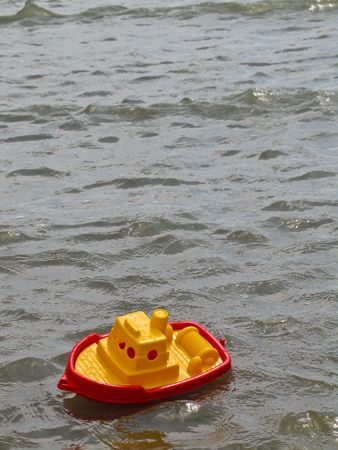 A red and yellow plastic toy fishing boat bobs in small waves in the ocean. Stock Photo
