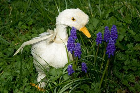 A handmade duck, made of straw and feathers,  beside purple flowers, amidst tall grass.