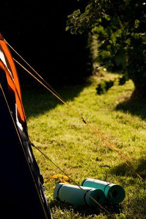 Une tente orange, vert ou bleu-up bedrolls roulé à côté de lui, dans une clairière dans la lumière du soir. Banque d'images - 4993965