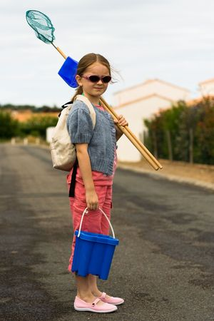 A girl pauses as she walks to the beach with a bucket, shovel, and net.