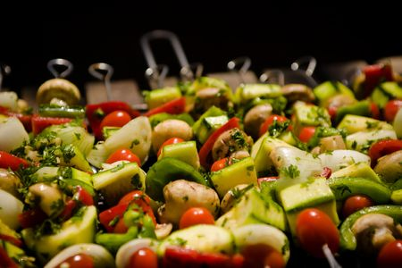Various colorful and healthy vegetables grill in a barbecue. Shish-kebabs made with mushrooms,peppers,cherry tomatoes,zuccini squash, and onions. Stock Photo