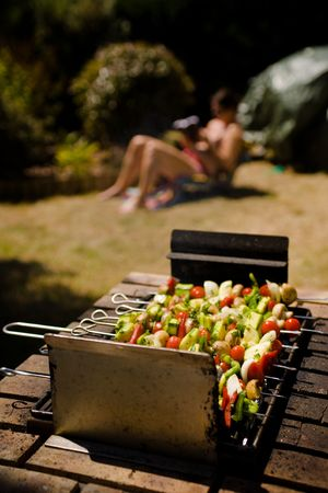 Various colorful and healthy vegetables grill in a barbecue. Shish-kebabs made with mushrooms,peppers,cherry tomatoes,zuccini squash, and onions. A young woman appears in the background, reading whlie reclining on a beach chair.