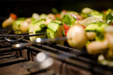 Various colorful and healthy vegetables grill in a barbecue. Shish-kebabs made with mushrooms,peppers,cherry tomatoes,zuccini squash, and onions. Closeup of the metal spits.