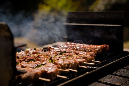 Orderly rows of meat on metal spits, in a not bbq grill, outside during the Summer.  Sausages, chicken.