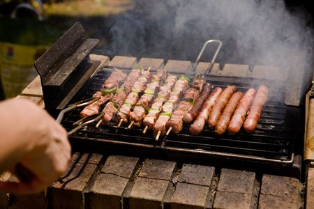 Orderly rows of meat on metal spits, in a not bbq grill, outside during the Summer.  Sausages, chicken. A hand approaches from the left, to serve the meat. Banque d'images