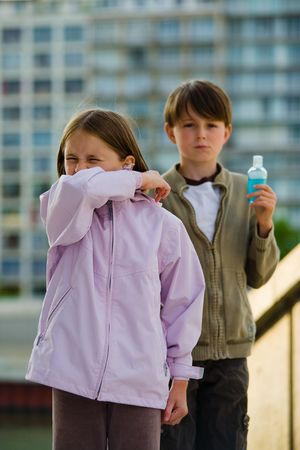 Two children stand in an urban setting, one sneezing into their elbow, the other holding a bottle of soapless hand cleanser. Stock Photo
