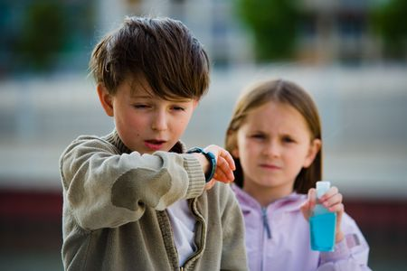 cleanser: Two children stand in an urban setting, one sneezing into their elbow, the other holding a bottle of soapless hand cleanser. Stock Photo