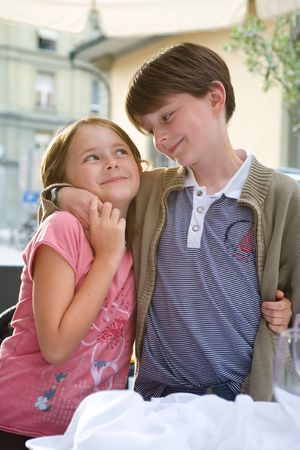 A boy and girl, brother and sister, share a hug and a tender smile.  Outside, summer urban setting.  Portrait, light tones. Stock Photo