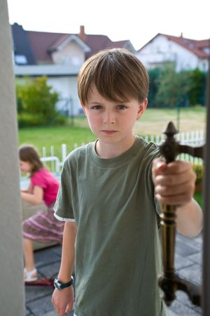 A boy in a green t-shirt stands in an open door with an angry, troubled expression on his face, while his sister appears indistinctly in the background.  The brother and sister have been arguing, and he is angry. photo