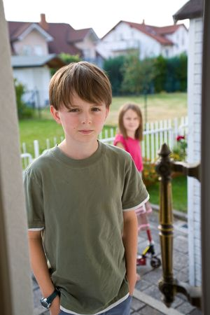 A boy in a green t-shirt stands in an open door with an angry, troubled expression on his face, while his sister appears indistinctly in the background.  The brother and sister have been arguing, and he is angry.