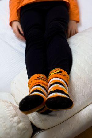 Closeup of a girls black leggings and Halloween socks, with a pumpkin and candy corn motif. Only her legs and hands are visible, with her feet in focus in the foreground.