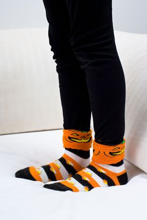 Closeup of a girl's black leggings and Halloween socks, with a pumpkin and candy corn motif. ONly her legs to mid-thigh are visible.