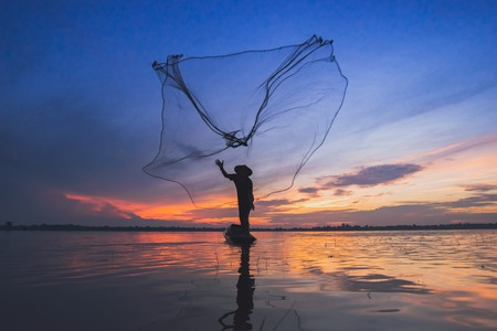 Asian fisherman on wooden boat casting a net for catching freshwater fish in nature
