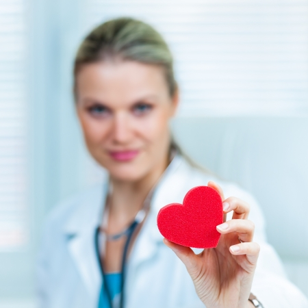 outpatient: Pretty Young Female Doctor Is Showing a Red Heart in Ambulance  shallow depth of field, color toned image