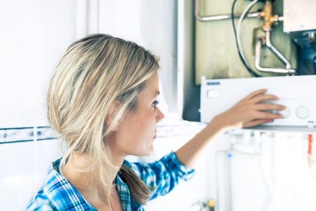 home heating: Beautiful Girl Is Seting Up a Boiler for the Winter