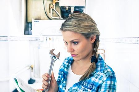 pompe: Bella Ragazza � imparare a riparare una caldaia Utilizzando una chiave a tubo Archivio Fotografico