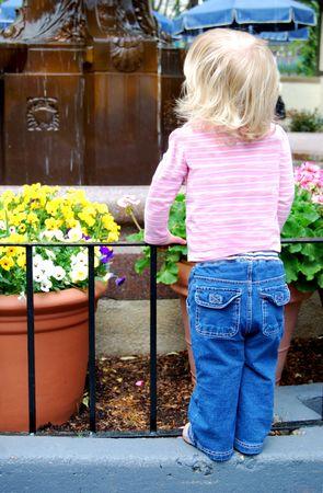 little girl watching water fountain