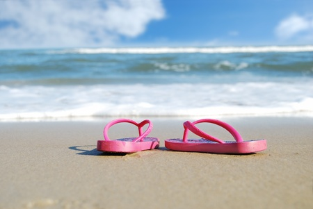 water shoes: flip flops on the edge of the ocean