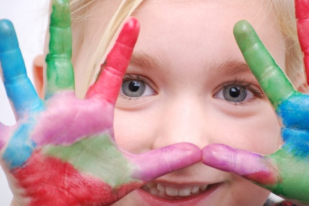 messy paint: little girl with paint on hands-focus on eyes Stock Photo