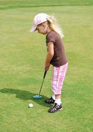 putting green: child putting golf ball Stock Photo