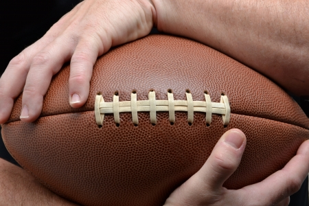 holding arm: man holding a football