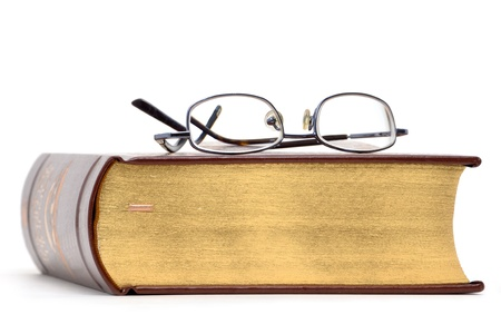 eyeglasses on a book white background