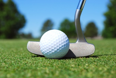 golf ball and putter on green photo