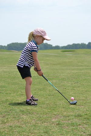 little girl ready to hit golf ball