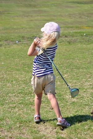 小さな女の子のゴルフ ・ ボールを打つ